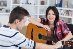Fille jouant la guitare pour l'ami à la maison Photos stock