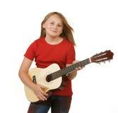 Fille jouant la guitare sur le blanc image libre de droits