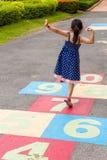 Fille jouant le jeu de marelle/fille jouant le jeu de marelle sur le terrain de jeu Photo libre de droits