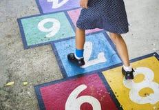 Fille jouant le jeu de marelle sur une rue Images libres de droits