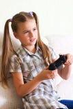 Fille jouant le jeu vidéo. Photographie stock
