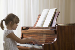 Fille jouant le piano Images stock