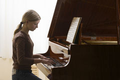 Fille jouant le piano Photographie stock libre de droits