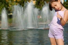 Fille jouant par la fontaine d'eau Photographie stock