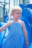 Fille jouant sur la glissière sur le terrain de jeu image libre de droits