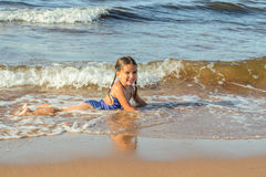 Fille jouant sur la plage Photo stock