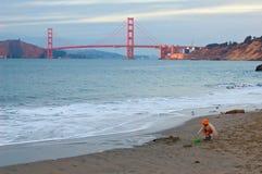 Fille jouant sur la plage au pont en coucher du soleil et en porte d'or Photographie stock