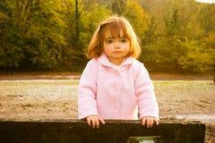 Fille jouant sur le banc Photos libres de droits