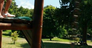 Fille jouant sur un tour de terrain de jeu en parc banque de vidéos