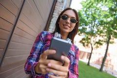 Fille joyeuse à l'aide du smartphone dehors Image libre de droits