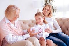 Fille joyeuse avec plaisir recevant un cadeau Images stock