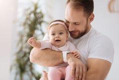 Fille joyeuse d'enfant en bas âge ayant l'amusement dans les bras du père Photographie stock libre de droits