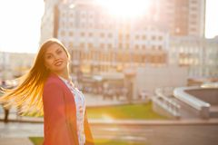 Fille joyeuse de brune avec les cheveux de flottement posant au fond de ville de tache floue L'espace pour le texte image libre de droits