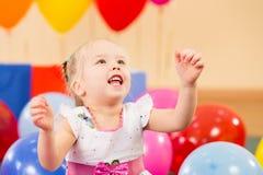 Fille joyeuse de gosse avec des ballons sur la fête d'anniversaire Image libre de droits