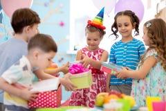 Fille joyeuse de petit enfant recevant des cadeaux ? la f?te d'anniversaire Vacances, concept d'anniversaire image stock