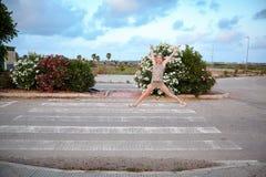 Fille joyeuse sautant sur la route Photo libre de droits