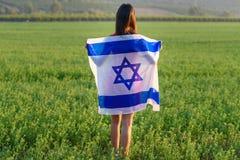 Fille juive avec le drapeau de l'Isra?l sur le paysage stup?fiant en bel ?t? photographie stock libre de droits