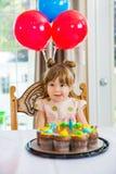 Fille léchant des lèvres en Front Of Birthday Cake Photo libre de droits