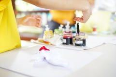 Fille laissant tomber la couleur sur le morceau de tissu blanc Art et concept d'atelier photographie stock libre de droits