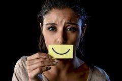 Fille latine déprimée triste latine tenant le papier cachant sa bouche derrière le sourire dessiné par faux photo stock
