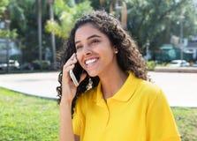 Fille latino-américaine heureuse avec de longs cheveux foncés parlant au téléphone Image stock