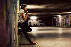 Fille élégante se tenant dans le tunnel grunge de graffiti, ville d'hutte Images stock