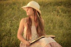 Fille lisant le livre sur le paysage rural au pré Images stock