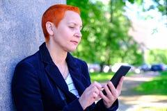 Fille lisant SMS dans le smartphone L'?motion de la surprise joyeuse La coupe de cheveux courte des femmes Profil ?l?gant ? la mo photo stock