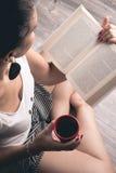 Fille lisant un livre avec une tasse de café Photographie stock libre de droits