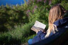 Fille lisant un livre en parc sur le banc Photos stock