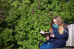 Fille lisant un livre en parc sur le banc Photos libres de droits