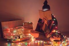 Fille lisant un livre sous la couverture à la maison Photos stock