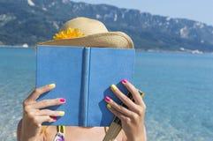 Fille lisant un livre sur la plage Photo stock