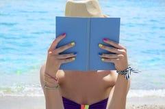 Fille lisant un livre sur la plage Images libres de droits