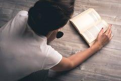 Fille lisant un livre sur le plancher Image libre de droits
