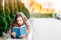 Fille lisant un livre tout en se trouvant sur le banc en parc Photographie stock