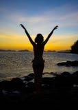 Fille méditant au coucher du soleil Image stock