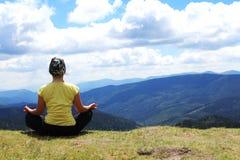 Fille méditante en montagnes Photo stock