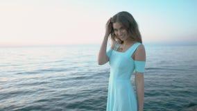 Fille magnifique dans une robe bleue posant tout en se tenant prêt la mer banque de vidéos