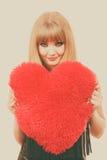 Fille magnifique de femme tenant le symbole rouge d'amour de coeur Photo stock