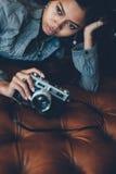 Fille magnifique se trouvant sur le sofa en cuir avec l'appareil-photo de photo dans des ses mains image stock