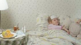 Fille malade avec la fièvre Enfant avec la fièvre : une femme s'inquiétant d'un enfant et de traiter avec des médicaments banque de vidéos