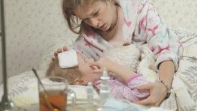 Fille malade avec la fièvre Enfant avec la fièvre : une femme s'inquiétant d'un enfant et de traiter avec des médicaments clips vidéos