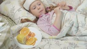Fille malade avec la fièvre Un enfant avec la fièvre se situe dans le lit et mange du fruit banque de vidéos