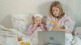 Fille malade avec une température L'enfant avec la fièvre se situe dans le lit avec sa mère, mange du fruit et utilise un ordinat clips vidéos
