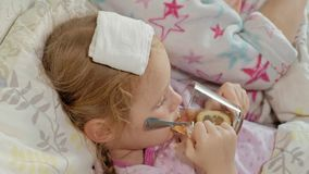 Fille malade avec une température L'enfant avec la fièvre se situe dans le lit avec sa mère, mange du fruit et utilise un ordinat banque de vidéos