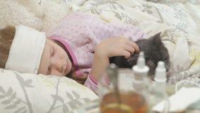 Fille malade avec une température Un enfant avec la fièvre se situe dans le lit avec un chat banque de vidéos