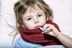 Fille malade se situant dans le lit avec un thermomètre dans la bouche Photos stock