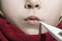 Fille malade se situant dans le lit avec un thermomètre dans la bouche Photos libres de droits