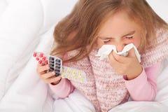 Fille malade sur le lit éternuant dans le mouchoir dans la chambre à coucher photos libres de droits